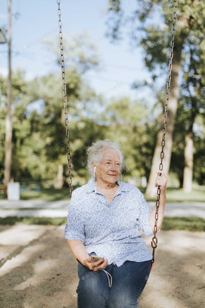 Happy elderly woman on a swing