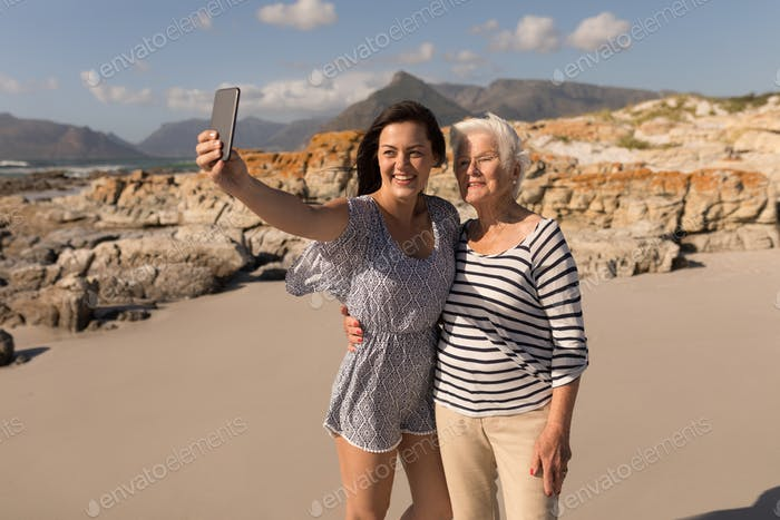 Front view of happy young woman taking selfie with her mother on beach in the sunshine