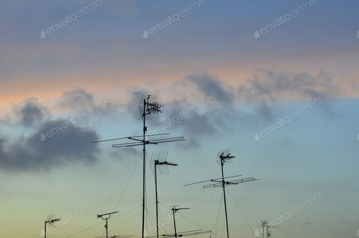 Silhouette of antennas against cloudy sky
