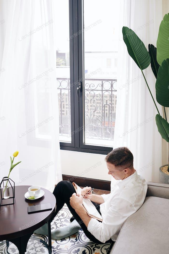 Young man filling gratitude journal