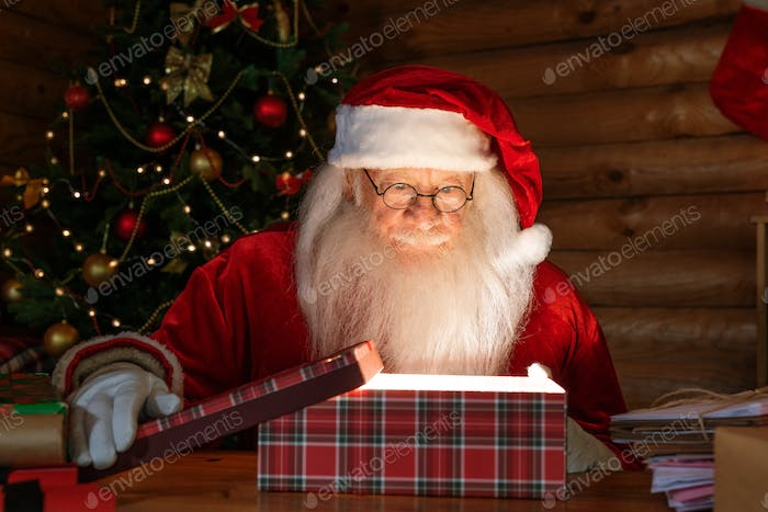 Happy Santa in costume and eyeglasses opening giftbox with magic light inside