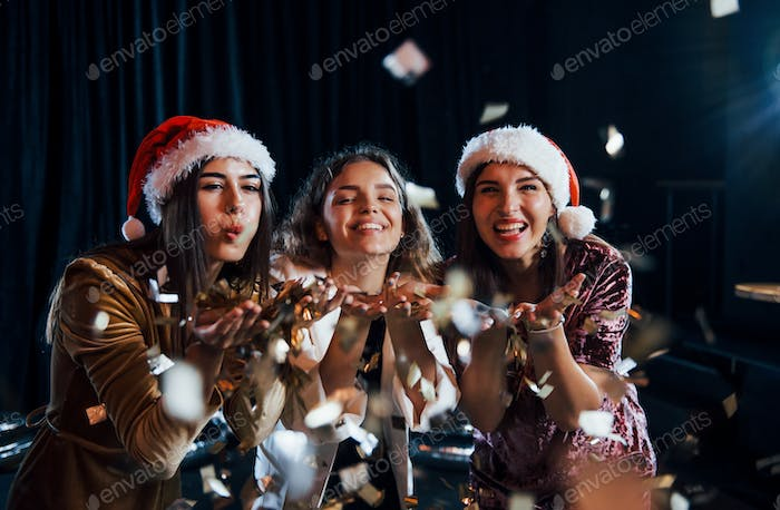 Three positive girls blowing gold colored confetti from their hands