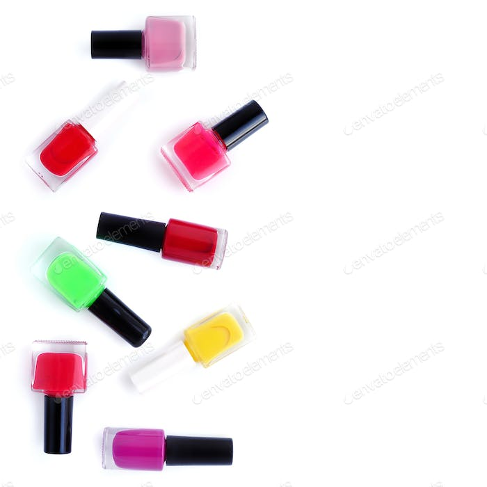 Coloured nail polish bottles on white background with copy space