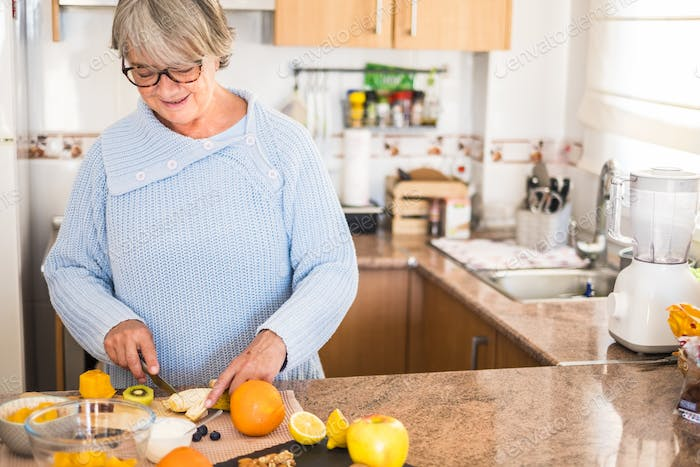 grandmother with glasses cut fruit and smiling - lifestyle health, healthy
