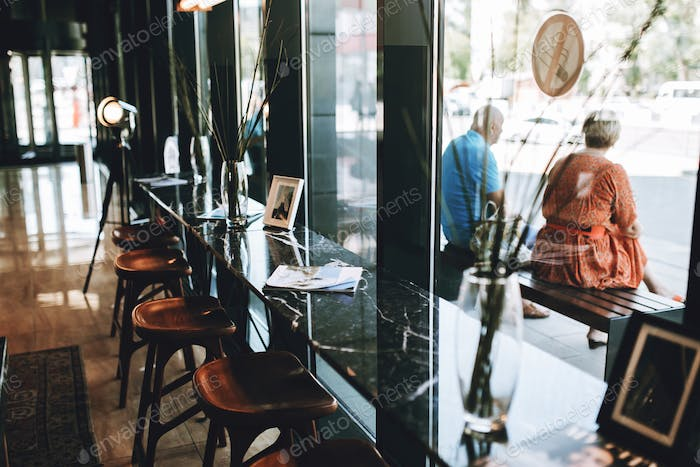 Tables with chairs are shown,situated next to a glass wall. Lovely atmosphere of the coffee shop is