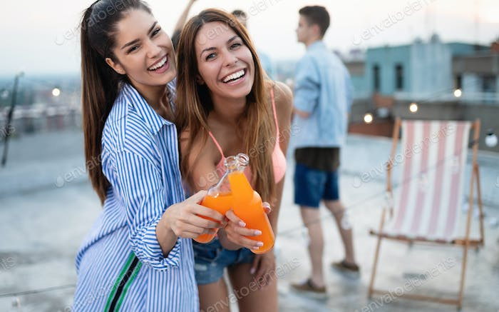 Beautiful women friends on the balcony having fun at party