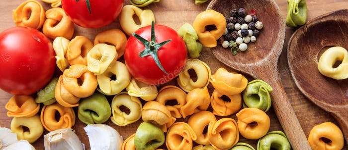 Colorful tortellini pasta, tomatoes and garlic on wooden table, banner