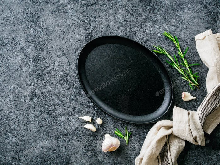 empty oval cast iron frying pan on dark grey concrete background, top view, blank space for text