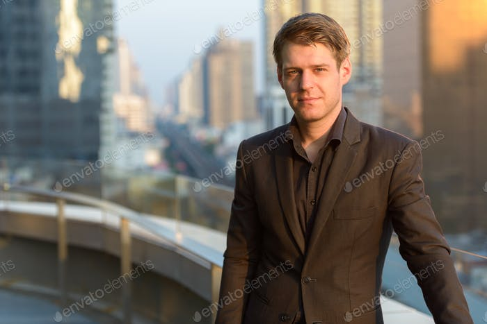Young handsome businessman against view of the city
