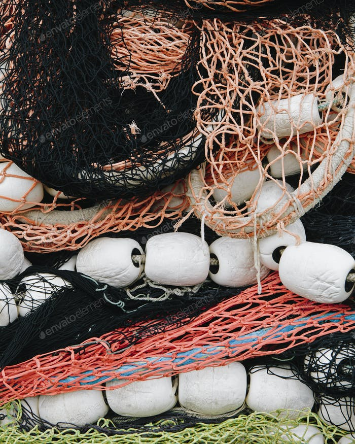 Pile of commercial fishing nets, with white floats, on the quayside