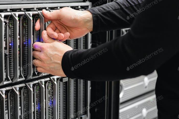 Männlicher IT-Ingenieur ersetzt Blade-Server im SAN im Rechenzentrum