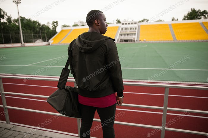 Back view of a young african sportsman standing at the stadium