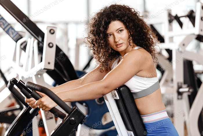 Good fit curly girl dressed in sports clothes is doing exercise on the sports equipment in the