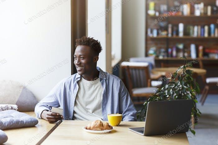 Chico afroamericano milenario con smartphone y portátil disfrutando de café por la mañana y croissant en