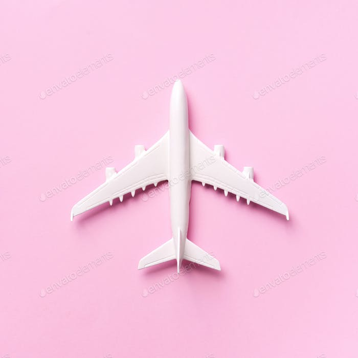 Travel, vacation concept. White model airplane on pastel pink color background with copy space. Top