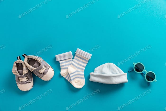 Baby boy clothes and accessories on bright blue background