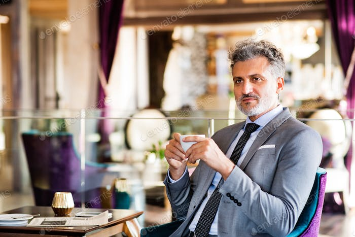 Mature businessman with coffee in a hotel lounge.