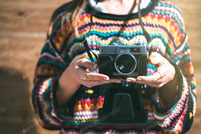 cropped woman with vintage old camera and colorful sweater