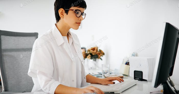 Beautiful female doctor typing receipt for patient