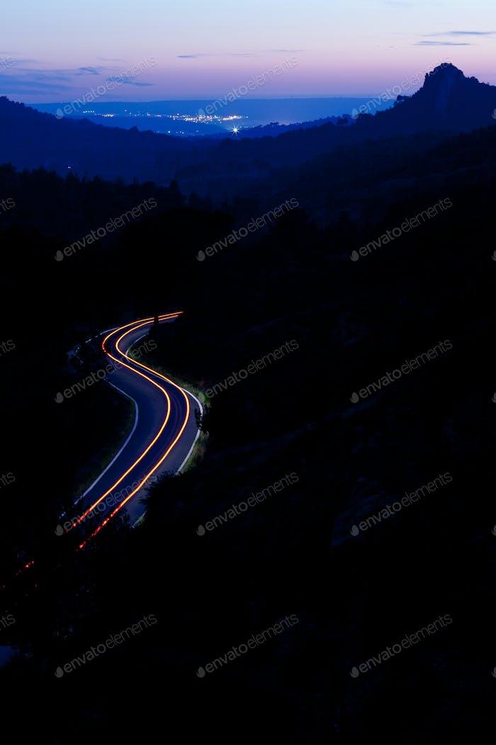 Bergstraße in der Nacht mit Autos bewegen sich schnell (farbgetöntes Bild)