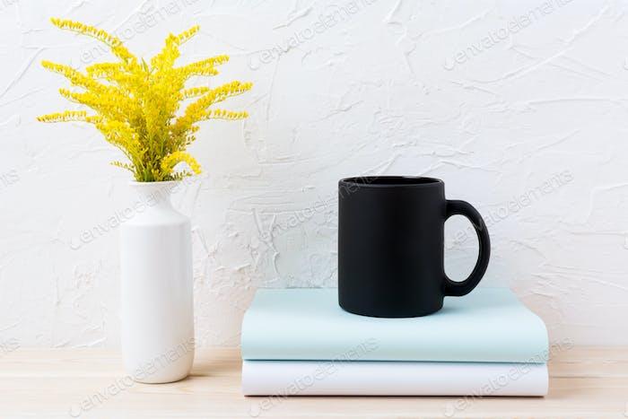 Black coffee mug mockup with ornamental golden grass and books