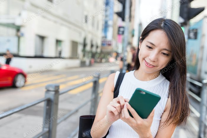 Woman looking for location on cellphone in Hong Kong
