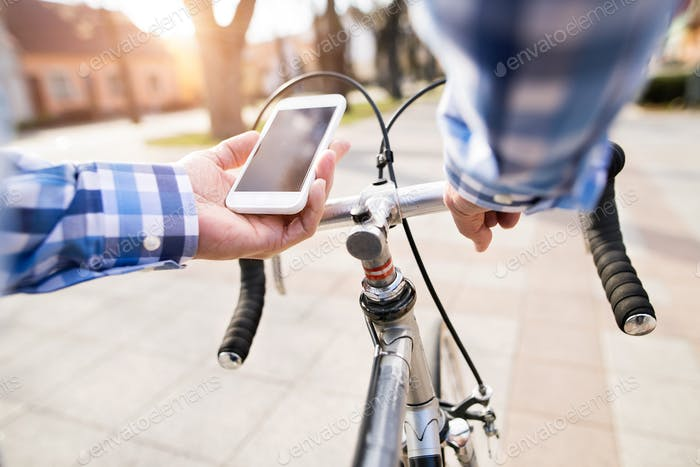 Senior man with smartphone riding bicycle in town.