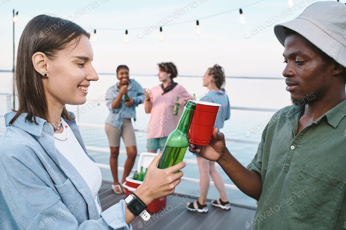 Young intercultural dates clinking with drinks against their friends