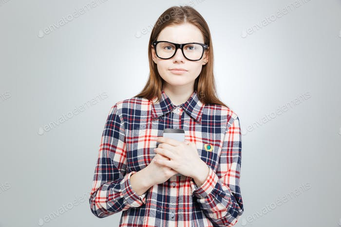 Serious beautiful teenage girl in glasses snading and holding smartphone