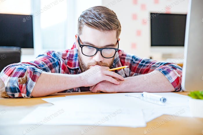 Thoughtful bearded man in glasses working with blueprits