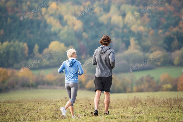 Young couple running in autumn nature, rear view