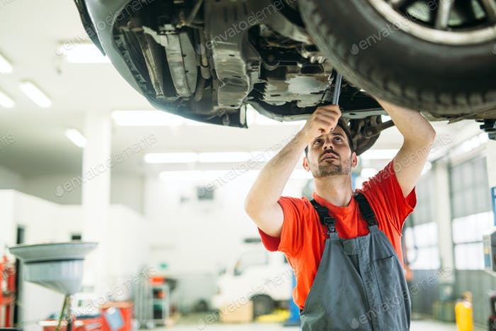 car service, repair, maintenance and people concept - happy smiling auto mechanic man at workshop