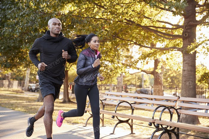 Young black couple jogging in a Brooklyn park, three quarter length