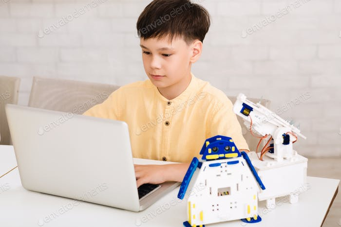 Schoolboy constructing robotic toys and using laptop