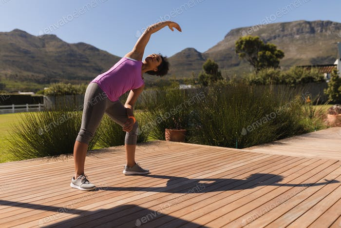 Young woman performing stretching exercise in the backyard
