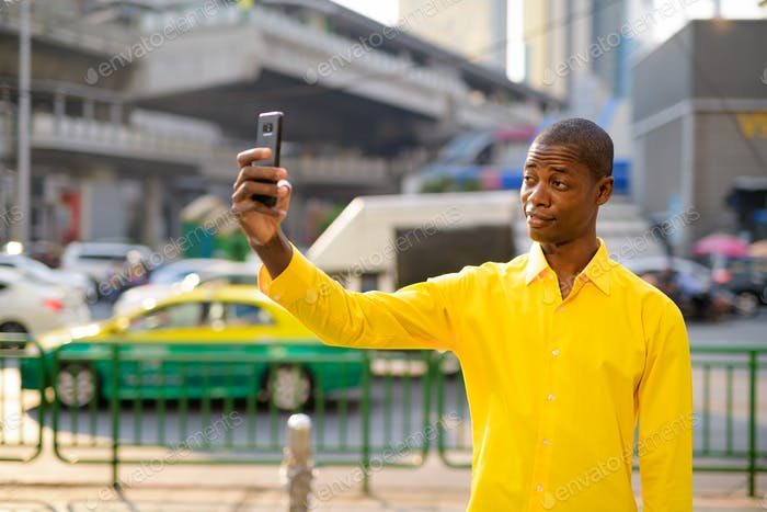 Happy young bald African businessman taking selfie in the city streets outdoors