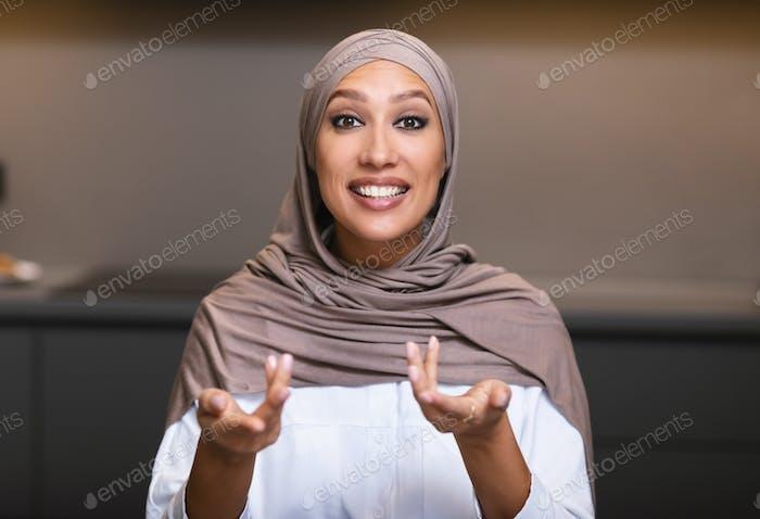 Muslim Woman Talking Looking At Camera Sitting In Kitchen Indoor