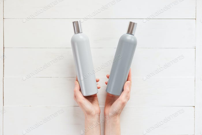 The woman chooses one of the two shampoos in the bottle