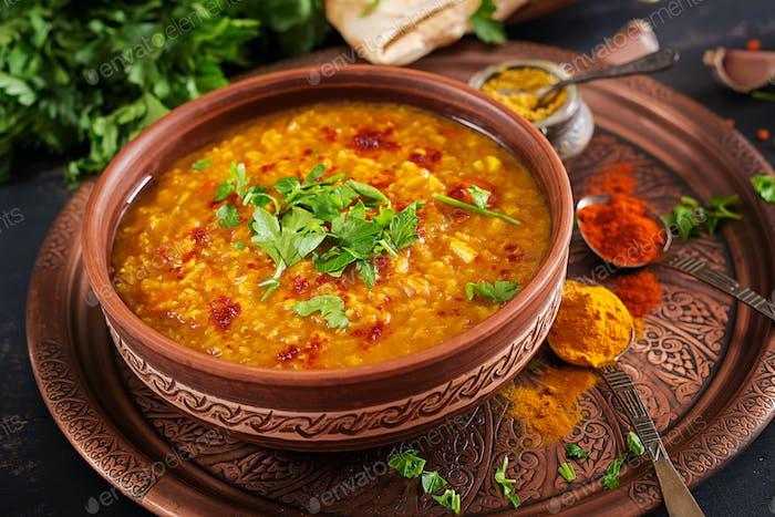 Indian Dhal würziges Curry in Schüssel, Gewürze, Kräuter, rustikaler schwarzer Holzhintergrund.