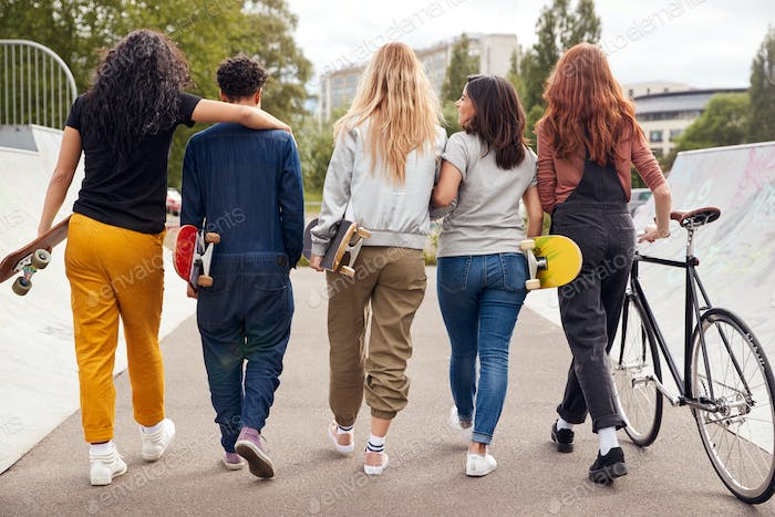 Rear View Of Female Friends With Skateboards And Bike Walking Through Urban Skate Park