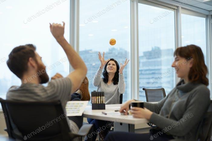 Drei Geschäftsleute, zwei Frauen und ein Mann, der bis zum Ball reicht.