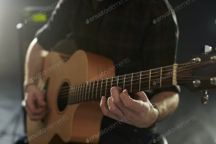 Close Up Of Man Playing Acoustic Guitar In Studio
