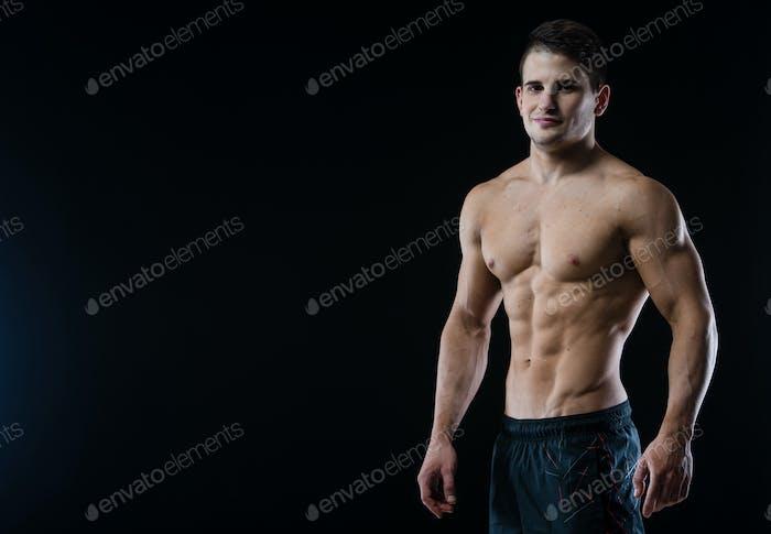 Молодые и подходят мужчина модель позирует его мышцы глядя прямо на камеру