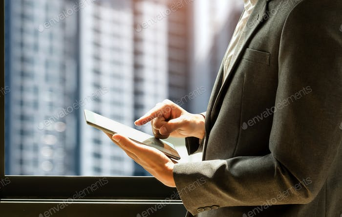 Businessman wearing suit is using tablet,man stands by the window.