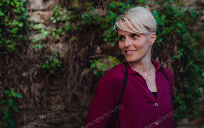 A portrait of woman standing outdoors, looking away. Copy space
