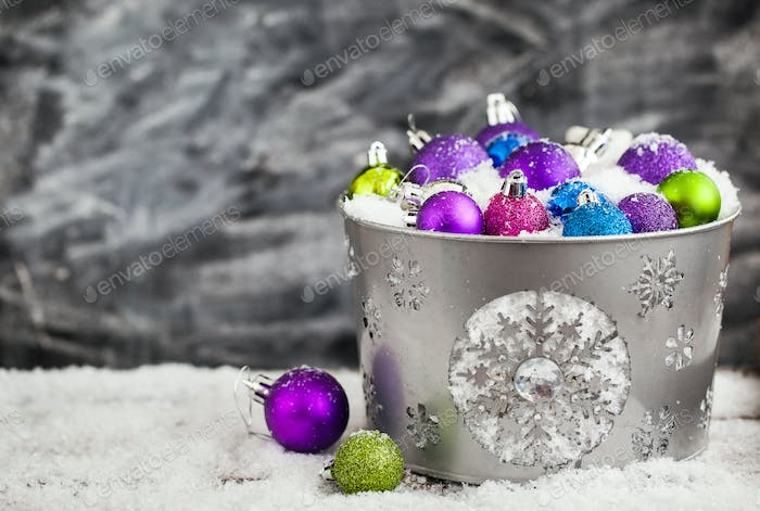 Christmas balls in snow covered bucket