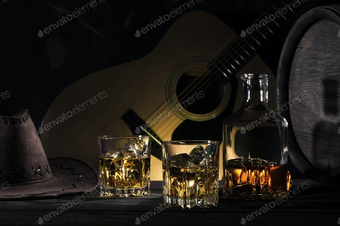 Two glasses of whiskey with ice and cowboy hat on wooden table