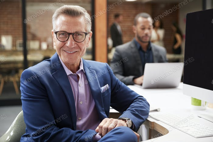 Portrait Of Mature Businessman Working At Desk On Computer In Open Plan Office With Colleagues