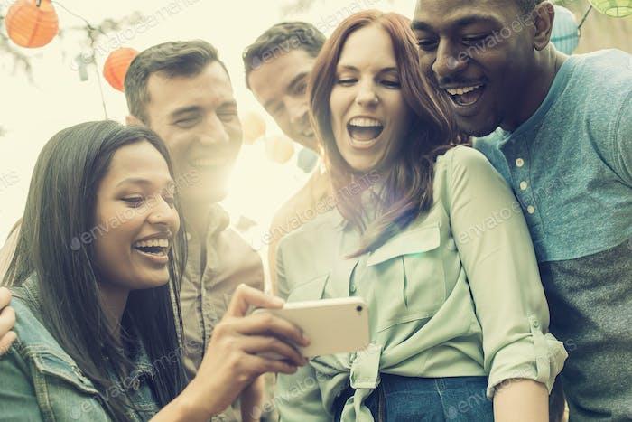 Um grupo de amigos se reunindo para tirar uma selfie em grupo.