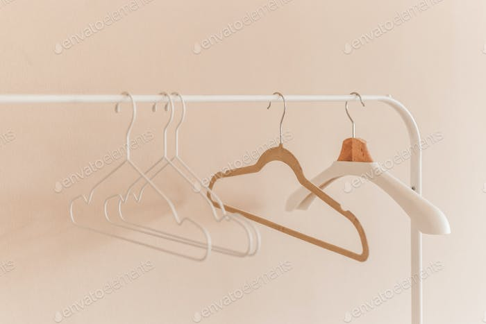 wooden coat hangers on clothes rail.